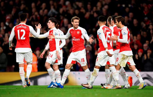 Joel Campbell (hidden) celebrates scoring the first goal for Arsenal with team mates