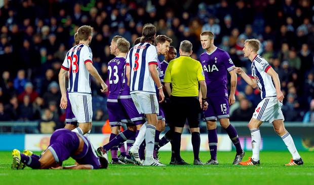 Players surround referee Jonathan Moss before showing West Brom's James McClean (not pictured) a yellow card after fouling Tottenham's Mousa Dembele (bottom) Reuters / Eddie Keogh Livepic