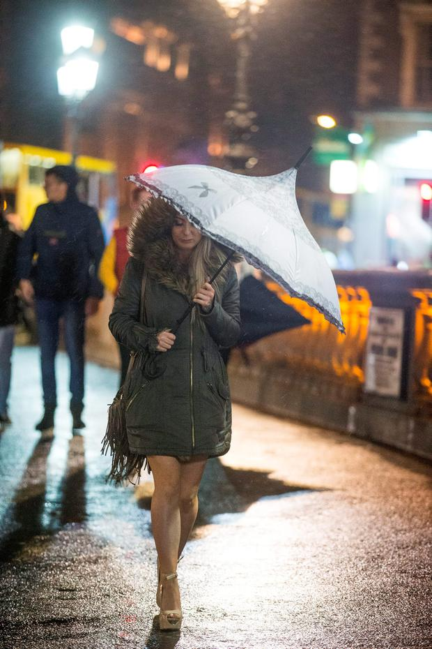 4/12/15 Dubliners brave the weather for a night out at O'Connell bridge in Dublin. Picture: Arthur Carron