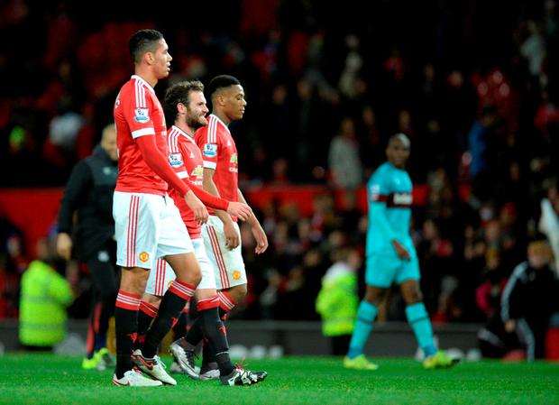 (L-R) Manchester United's English defender Chris Smalling, Manchester United's Spanish midfielder Juan Mata and Manchester United's French striker Anthony Martial walk off the pitch after the English Premier League football match between Manchester United and West Ham United at Old Trafford in Manchester, north west England, on December 5, 2015. AFP PHOTO / OLI SCARFF RESTRICTED TO EDITORIAL USE. No use with unauthorized audio, video, data, fixture lists, club/league logos or 'live' services. Online in-match use limited to 75 images, no video emulation. No use in betting, games or single club/league/player publications.OLI SCARFF/AFP/Getty Images