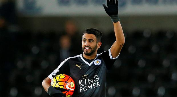 Leicester City's Riyad Mahrez celebrates with the match ball after the game after scoring a hat trick