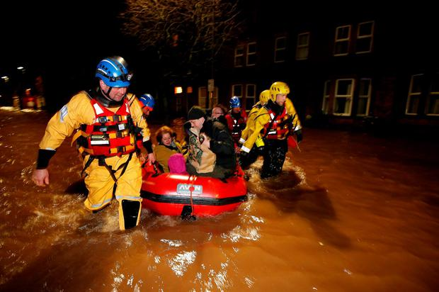 A family and their dog are rescued by the coastguard on Warwick Road in the centre of Carlisle after heavy rain from Storm Desmond tore through Britain, bringing strong winds and heavy rain which caused Cumbria to declare a major incident