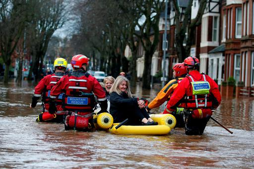 Emergency workers use an inflatable raft to rescue two women from floodwater on Warwick Road in Carlisle, after heavy rain from Storm Desmond tore through Britain, bringing strong winds and heavy rain which caused Cumbria to declare a major incident