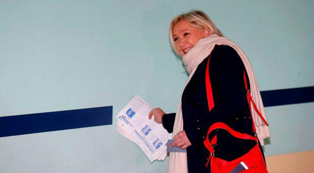French National Front political party leader and candidate Marine Le Pen collects ballots as she arrives at a polling station during the first round of the regional elections in Henin-Beaumont, France, December 6, 2015