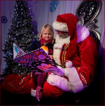 A very, very good girl: Isobel Conachy (5) enjoying a story from Santa at the Zoo last weekend. Photo: David Conachy.