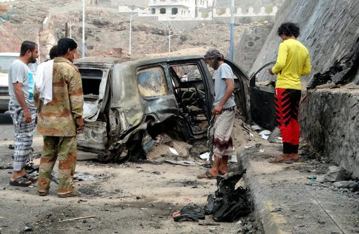 People look at the wreckage of a car at the site of the car bomb attack that killed Jaafar Mohammed Saad