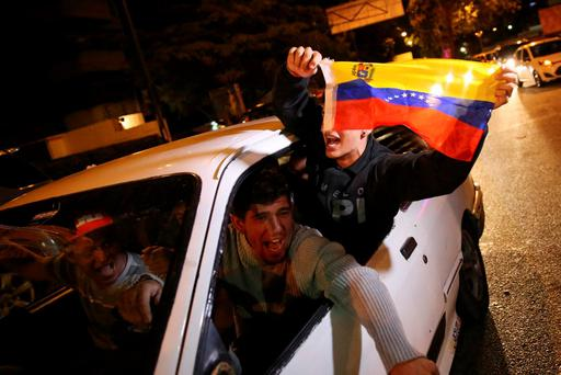 Supporters of the opposition Democratic Unity coalition wave a Venezuelan national flag from a car while they celebrate their victory on a street in Caracas December 7, 2015