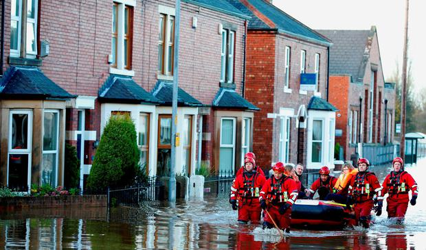 Rescue workers help residents to safety in Carlisle, after heavy rain from Storm Desmond tore through Britain, bringing strong winds and heavy rain which caused Cumbria to declare a major incident.