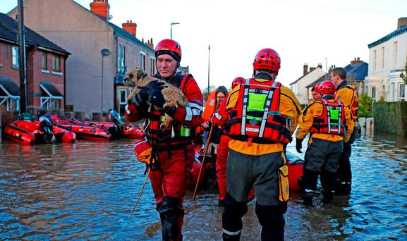 A rescue worker carries a dog in Carlisle, after heavy rain from Storm Desmond tore through Britain, bringing strong winds and heavy rain which caused Cumbria to declare a major incident. PRESS ASSOCIATION Photo. Picture date: Sunday December 6, 2015