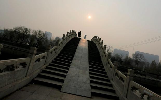 A man walks on a bridge on a hazy day in Beijing, China, December 7, 2015. REUTERS/Jason Lee