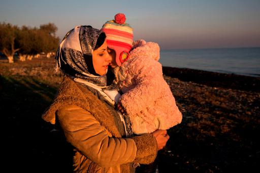 A woman holds her child on a beach near to the town of Mytilene after crossing a part of the Aegean sea on a dinghy, with other refugees and migrants, from Turkish coast to the Greek island of Lesbos, on December 7. (AP Photo/Santi Palacios)