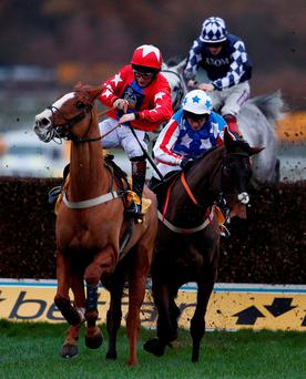 Jamie Moore riding Sire De Grugy, left, clear the last to win The Betfair Tingle Creek Steeple Chase from Special Tiara (second left) at Sandown