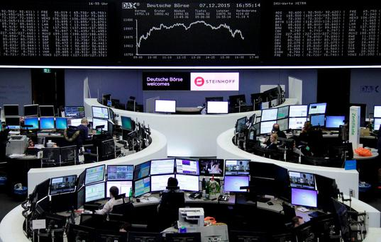 Traders work at their screens in front of the German share price index, DAX board, at the stock exchange in Frankfurt. Photo: Reuters