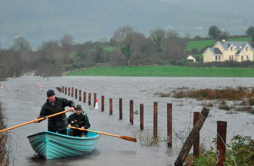 Gerard Mulqueen (right) makes his way through floods at Dooras, Co Clare, to get groceries to his mother Brett, assisted by neighbour James Peppard