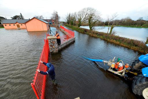 Garry Fitzgerald and Jonathan Fitzgerald from Blennerville battle to keep the water out of St Pat's GAA Club