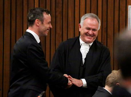 Oscar Pistorius (L) speaks with his defence advocate Barry Roux in the dock at the North Gauteng High Court in Pretoria, South Africa for a bail hearing, December 8, 2015