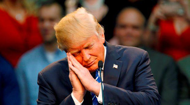 U.S. Republican presidential candidate Donald Trump gestures as if he is sleeping while talking about his opponent Jeb Bush