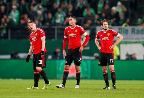 Manchester United's Bastian Schweinsteiger, Chris Smalling and Daley Blind look dejected against Wolfsburg
