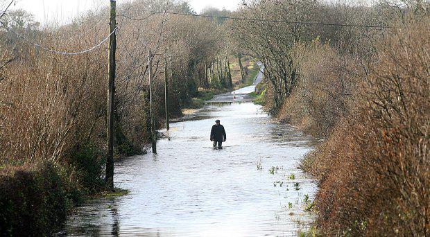 Richard Hazell, makes his way home through a flood near Cootehall, Co. Roscommon Photo Brian Farrell