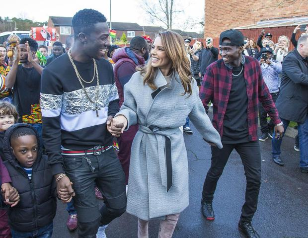Cheryl Fernandez-Versini's clip in hair extensions are on show as as she visits Farnborough with contestants Reggie and Bollie. Picture: FameFlynet