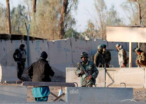 Afghan security forces stand guard at the entrance gate of Kandahar Airport where Taliban forces left 37 dead on Tuesday night Credit: Stringer (REUTERS)