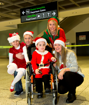 Left to right - Lucia Meehan (7) with brother Declan (5), dad Brian and mam Francis Meehan, with Elf helper Karin Arkins at Dublin Airport yesterday