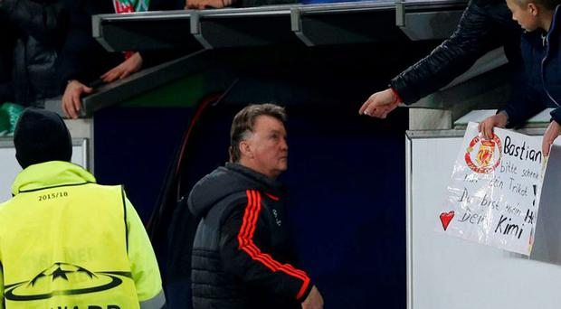 Fans gesture towards Manchester United manager Louis van Gaal as he walks down the tunnel at the Volkswagen-Arena on Tuesday night