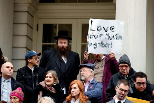 People opposed to Republican presidential hopeful Donald Trump's proposal to ban Muslims from entering the United States stand on the steps of New York's City Hall during an interfaith rally in Manhattan. Photo: Reuters