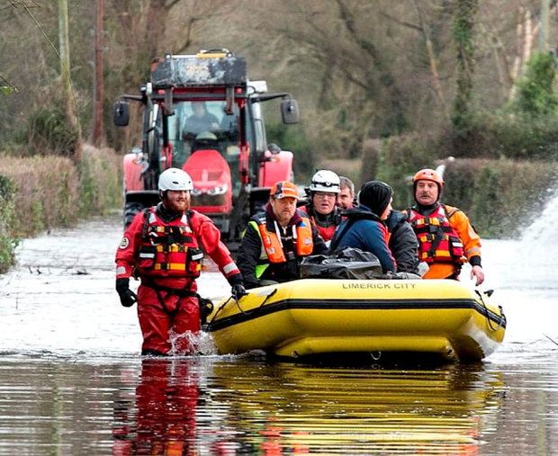 Mike Hogan with his sons Mark and Sean being rescued from their home in Springfield Clonlara, Co Clare, by Civil Defence officers yesterday