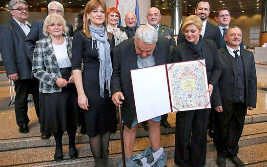 Ivan Zvonimir Cicak's trousers fell down while posing for a photo with Croatian President Kolinda Grabar-Kitarovic. Ivan, Croatia's leading rights group chief, was attending an event marking the forthcoming international human rights day in Zagreb. Photo: AFP/Getty Images