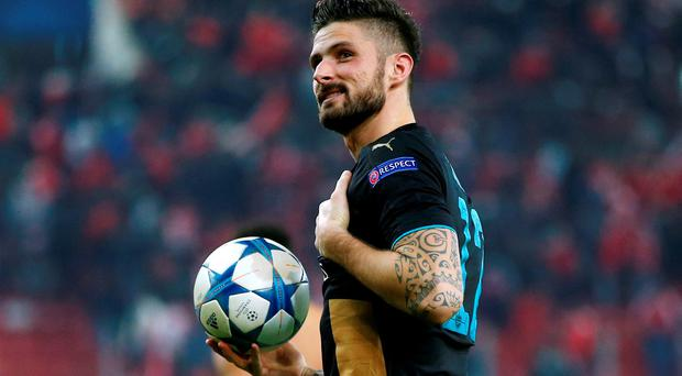 Arsenal's Olivier Giroud celebrates with the matchball after scoring a hat trick