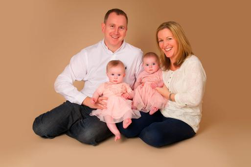 Alison pictured with her husband Neil and twins Meghan and Gemma, now 2