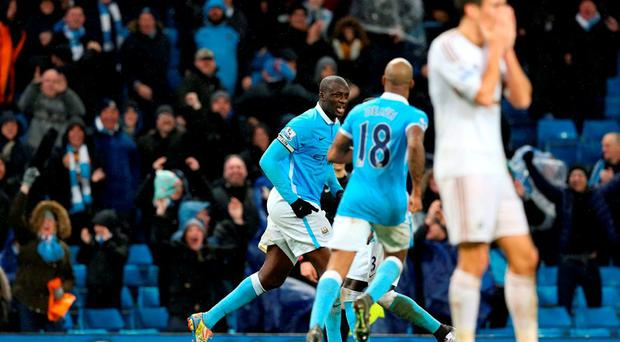 Manchester City's Yaya Toure (left) celebrates scoring his side's second goal of the game during the Barclays Premier League match at the Etihad Stadium
