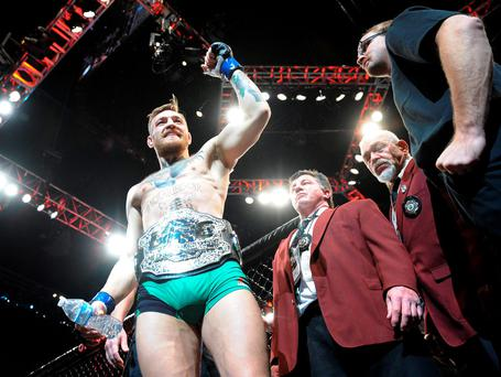 Conor McGregor exits the octagon following his championship victory against Jose Aldo during UFC 194 at MGM Grand Garden Arena. Mandatory Credit: Gary A. Vasquez-USA TODAY Sports