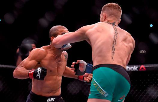 Conor McGregor, right, lands a left punch on Jose Aldo, resulting in a knock-out stoppage after 13 seconds of round one. UFC 194: Jose Aldo v Conor McGregor, MGM Grand Garden Arena, Las Vegas, USA. Picture credit: Ramsey Cardy / SPORTSFILE