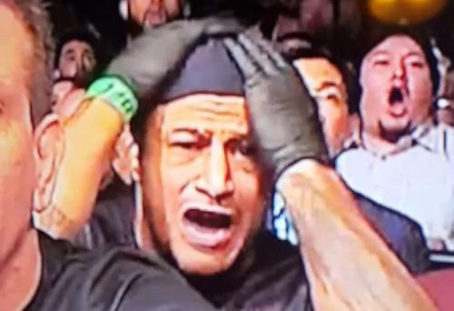A member of Jose Aldo's corner reacts to events in the octagon