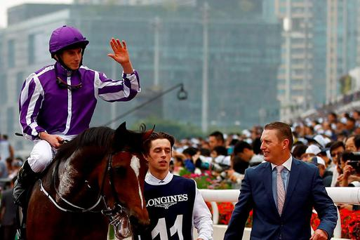 Ryan Moore (L) riding Highland Reel gestures after winning the Longines Hong Kong Vase race at Sha Tin Racecourse in Hong Kong