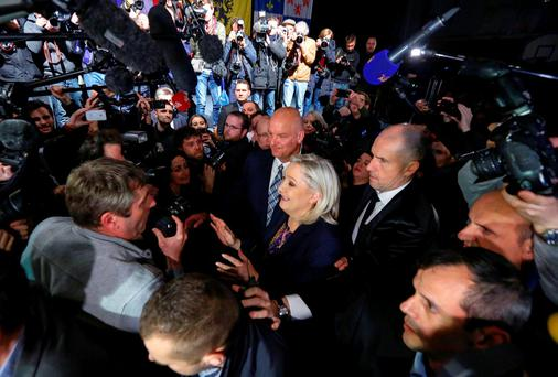Marine Le Pen (C), French National Front (FN) political party leader and candidate for the National Front in the Nord-Pas-de-Calais-Picardie region, is surrounded by journalists as she leaves after results in the second-round regional elections in Henin-Beaumont, France REUTERS/Yves Herman