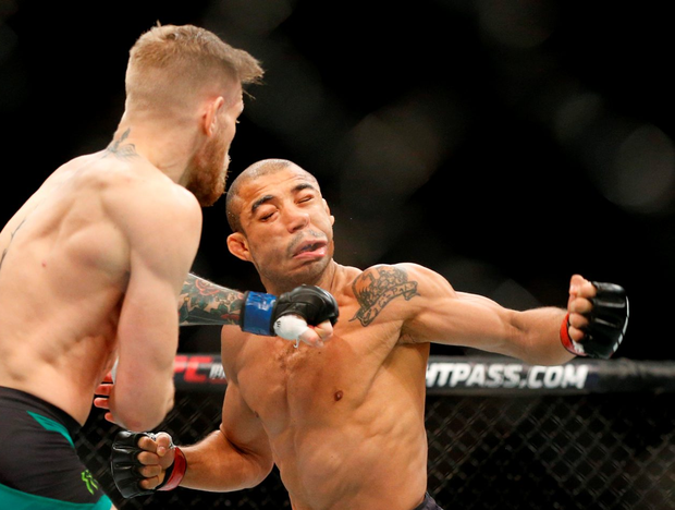 Conor McGregor, left, fights Jose Aldo during a featherweight championship mixed martial arts bout at UFC 194, Saturday, Dec. 12, 2015, in Las Vegas. McGregor stopped Aldo with one spectacular punch just 13 seconds into the first round Saturday night, backing up his bravado and claiming the undisputed featherweight title at UFC 194 on Saturday night. (AP Photo/John Locher)
