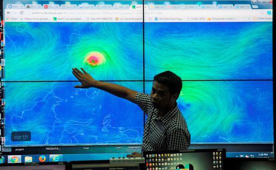 Meteorologists from the Philippine Atmospheric Geophysical and Astronomical Services Administration (PAGASA) monitor and plot the direction of powerful Typhoon Melor at their headquarters in suburban Manila on December 14, 2015. Photo: AFP/Getty Images