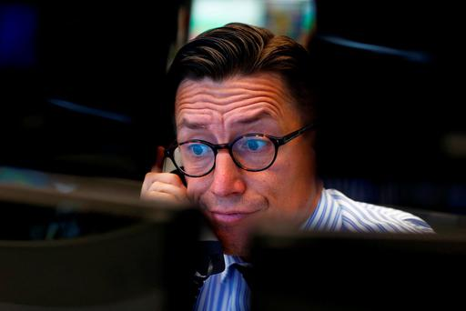 A trader speaks on the phone at his desk at the Frankfurt stock exchange. Photo: Reuters