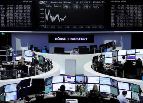 Traders work at their desks in front of the German share price index DAX board, at the stock exchange in Frankfurt. Photo: Reuters