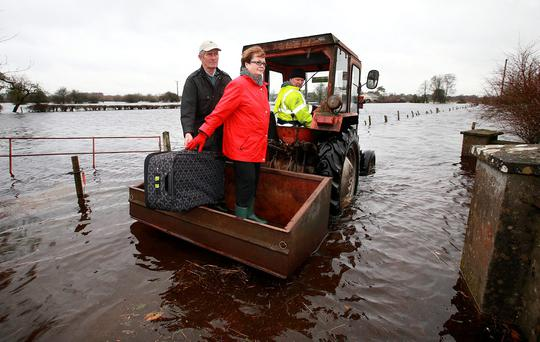 Michael and Patty Macken prepare to abandon their flooded home at Carrick O'Brien by tractor with the help of their son Paul. Photos: Frank Mc Grath