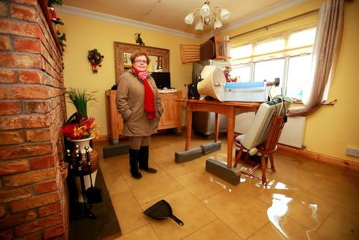 Breda Caulfield stands in her flooded kitchen, with furniture raised up on blocks, after floodwaters breached sandbags at her home on the Clonown Road in Athlone. Photo: Frank Mc Grath