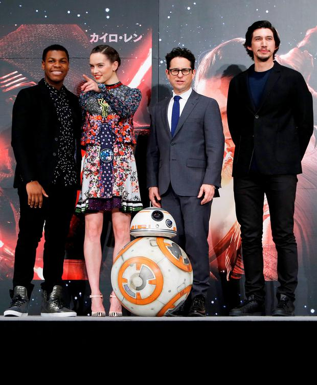 Director J.J. Abrams (2nd R), cast members John Boyega (L), Daisy Ridley (2nd L), and Adam Driver pose for pictures with Star Wars character BB-8 (C) during a news conference for their upcoming movie