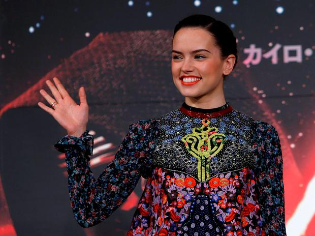 Cast member Daisy Ridley waves as she walks into a news conference for her upcoming movie