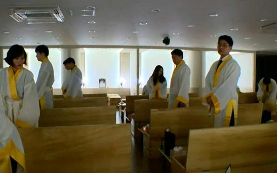 In a large room in a nondescript modern office block in Seoul, staff from a recruitment company are staging their own funerals Photo: Steve Evans / BBC News