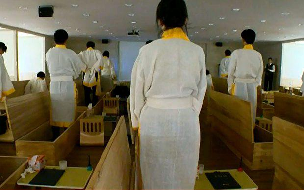 Dressed in white robes, they sit at desks and write final letters to their loved ones Photo: Steve Evans / BBC News