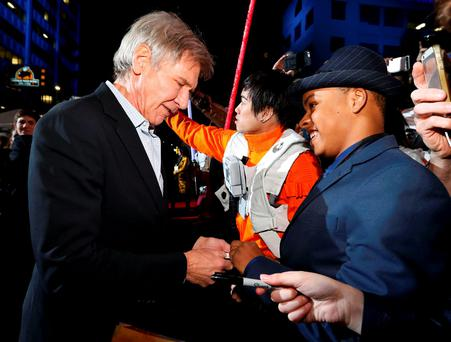 Actor Harrison Ford greets fans as he arrives at the premiere of
