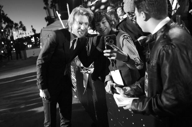 HOLLYWOOD, CA - DECEMBER 14: (EDITORS NOTE: Image has been shot in black and white. Color version not available.) Actor Domhnall Gleeson (L) takes a selfie with a fan during the World Premiere of Star Wars: The Force Awakens at the Dolby, El Capitan, and TCL Theatres on December 14, 2015 in Hollywood, California. (Photo by Charley Gallay/Getty Images for Disney)